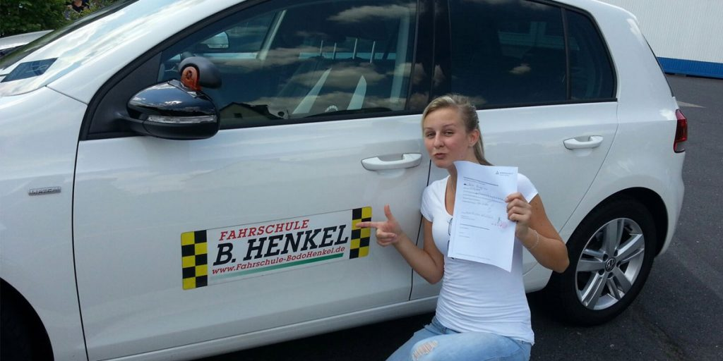 Glückliche Fahrschülerin vor weißem Fahrzeug - Fahrschule Leverkusen